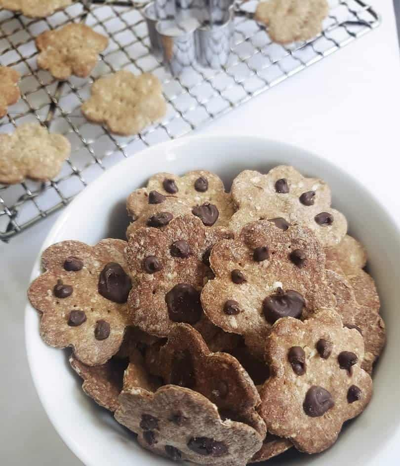 A white bowl filled with baked dog cookies shaped like paws.