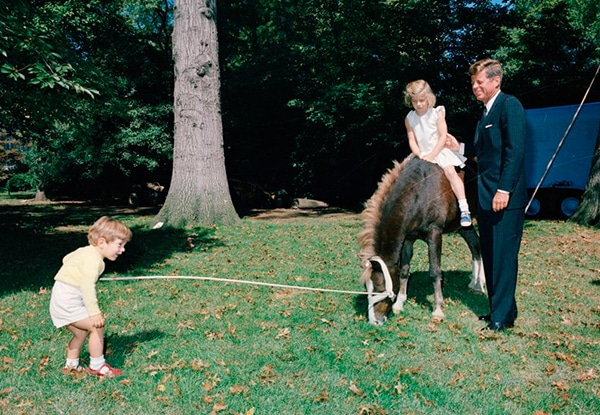 JFK with Caroline riding Leprechaun the horse and JFK Jr. off to the side
