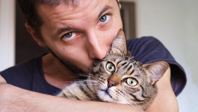 man hugs cat