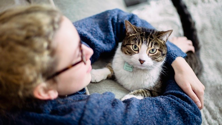 A girl wearing eyeglasses with her arms around her tabby cat