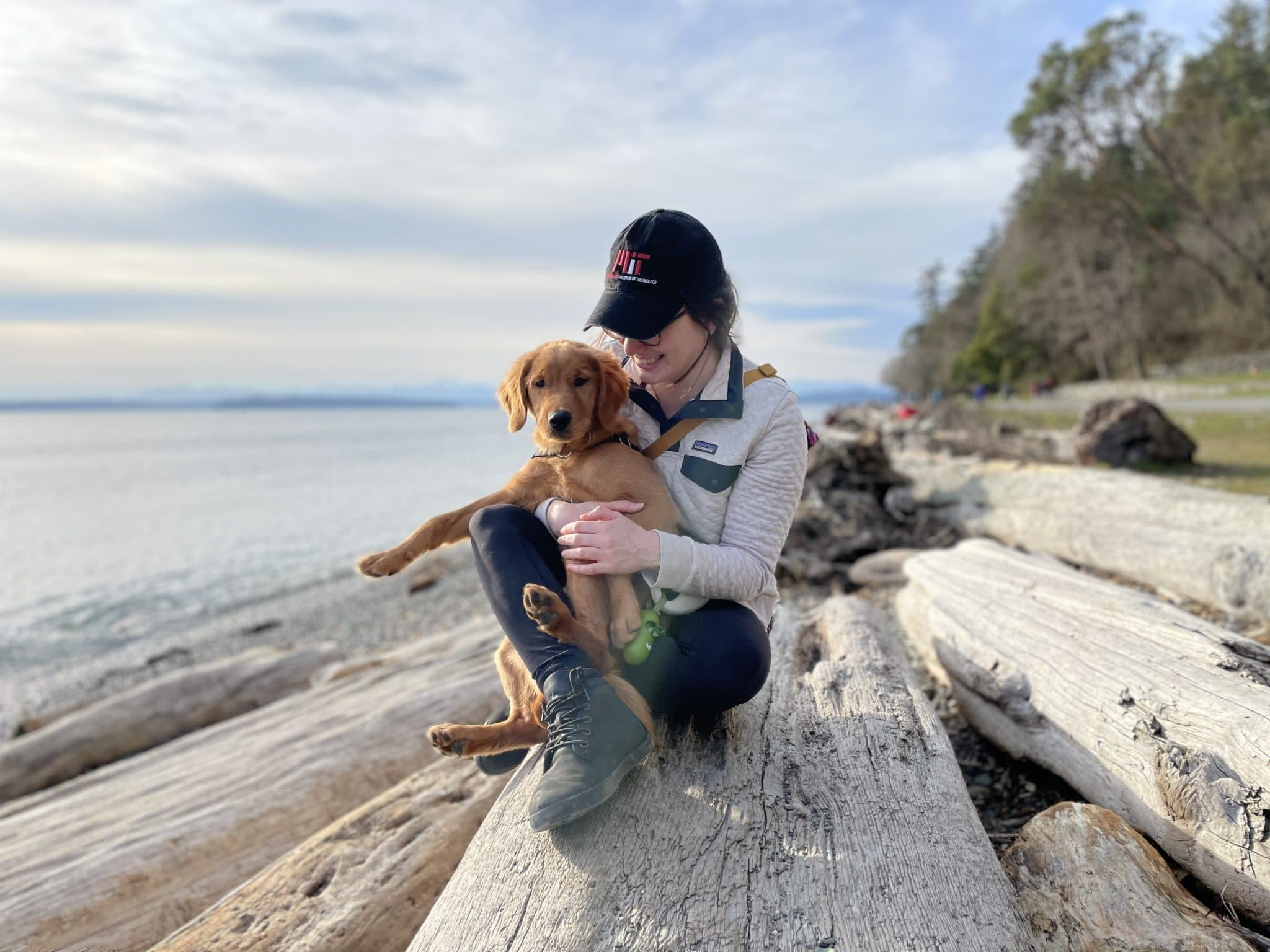 A woman on a long log, with her dog on the beach