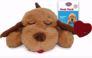 Smart Pet Love Snuggle Puppy Behavioral Aid Toy, plush sleeping puppy toy pictured with a heat pack and red heart-shaped gadget that pulses like a heartbeat