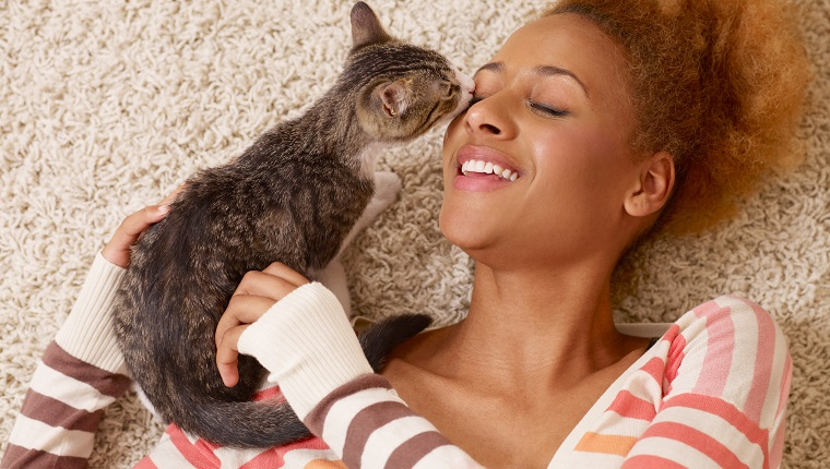 """""""portrait of attractive young african woman with curly hair laying in carpet, while playing with little cat"""""""
